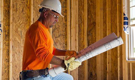 Aannemer bekijkt tekeningen voor aanbouw